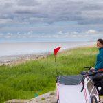 Junge Frau fährt Fahrrad mit befestigten Fahrradanhänger